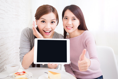 woman with phone: Two happy young female friends show empty digital tablet pc and show thumb up, great for your design, asian beauty Stock Photo