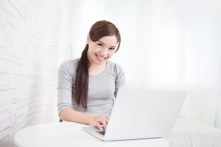 girl home: young woman use laptop and smile to you at home, asian beauty