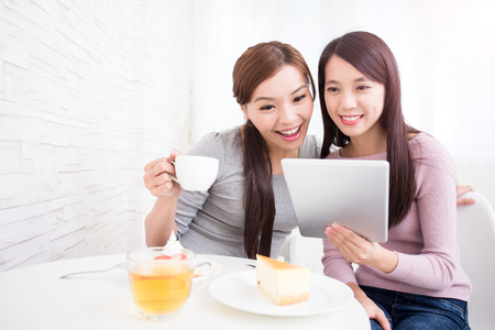 women coffee: Two happy young female friends use digital tablet pc with tea, coffee and cakes, healthy lifestyle and tecnology concept, asian beauty Stock Photo
