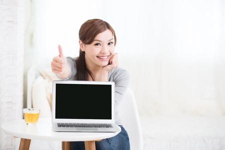 jovenes estudiantes: sonrisa joven mujer de uso portátil y mostrar la pantalla vacía en casa, belleza asiática