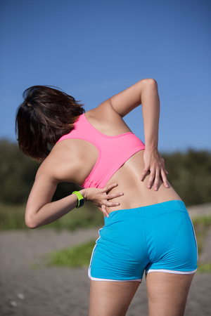 woman in pain: sport woman feel pain on back, health care concept, asian beauty
