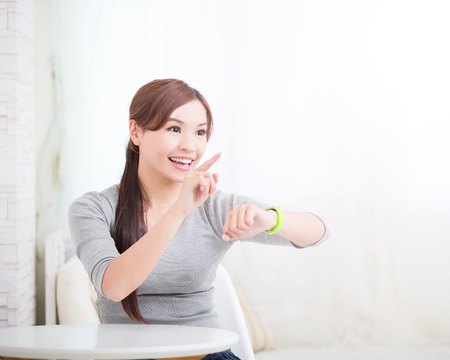 sport woman: smile young woman sit and use smart watch at home, healthy lifestyle concept, asian beauty Stock Photo