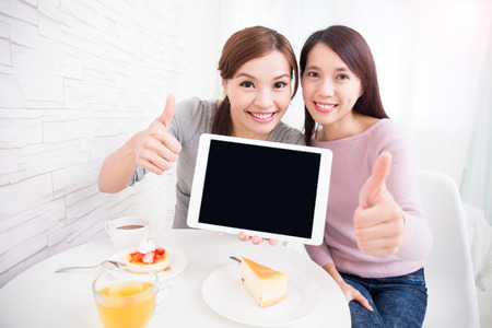 asia people: Two happy young female friends show empty digital tablet pc and show thumb up, great for your design, asian beauty Stock Photo