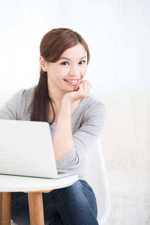 asian lifestyle: young woman use laptop and smile to you at home, asian beauty