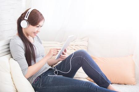 デジタル タブレットのソファで、アジアの美しさで音楽聴いて女性を笑顔します。