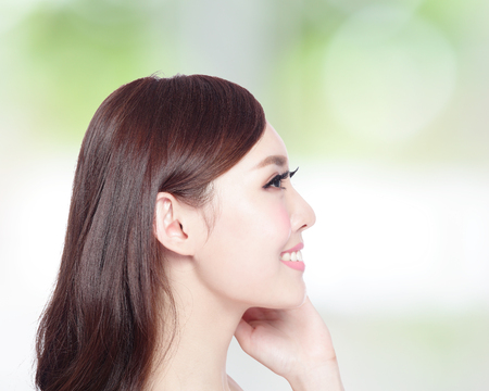 young asian: profile of beauty woman with health skin, teeth and hair isolated on green background, asian beauty