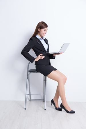 young asian: business woman sit with laptop computer with white wall background, great for your design or text, asian beauty Stock Photo