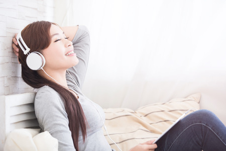smile woman listen to music in digital tablet on sofa, asian beauty