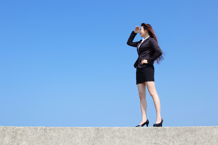 purpose: Successful business woman purposefully looking away with blue sky, asian beauty