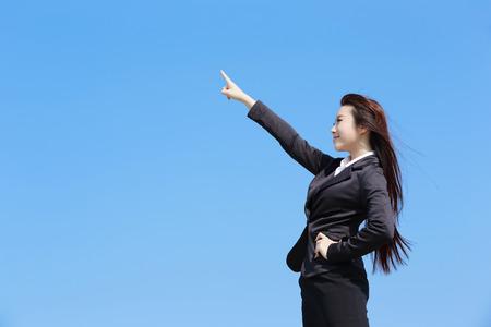 alzando la mano: Exitosa mujer de negocios que señala algo con el cielo azul, belleza asiática Foto de archivo