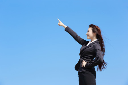 show of hands: Successful business woman pointing something with blue sky, asian beauty Stock Photo
