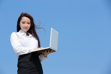 mujeres trabajando: Exitosa mujer de negocios mirando a otro lado a propósito y mantener un equipo con el cielo azul, belleza asiática