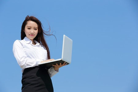 woman working: Successful business woman purposefully looking away and hold a computer with blue sky, asian beauty