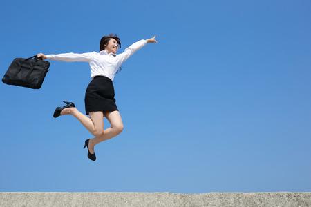 Succesvolle zakenvrouw springen en rennen met blauwe hemel achtergrond, volle lengte, aziatische Stockfoto