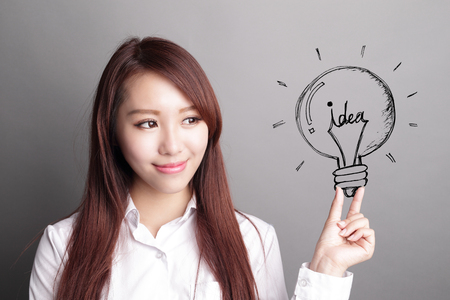 confident business woman hold light bulb isolated over gray background, asian beauty