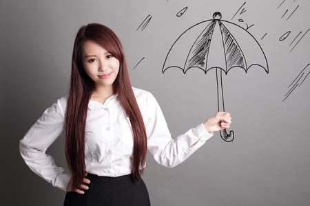 woman isolated: confident business woman hold umbrella isolated over gray background, asian beauty