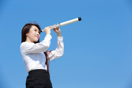 telescope: Business woman with telescope ( spyglass ) looking forward Prospects for future business with blue sky background, asian beauty