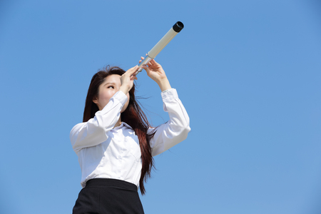 Business woman with telescope ( spyglass ) looking forward Prospects for future business with blue sky background, asian beauty