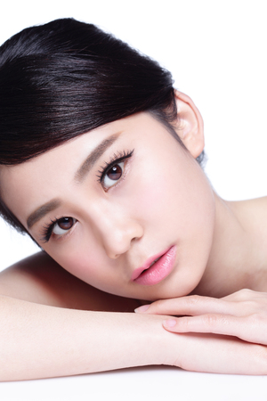 skin care woman: Charming woman skin care face close up while lying isolated on white background, asian girl