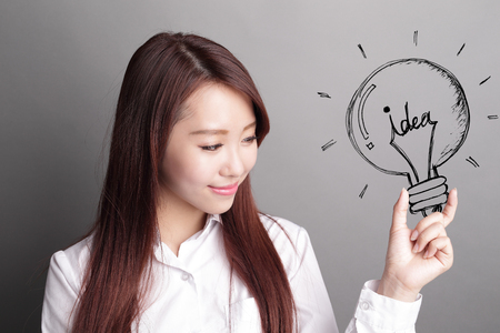 woman working: confident business woman hold light bulb isolated over gray background, asian beauty