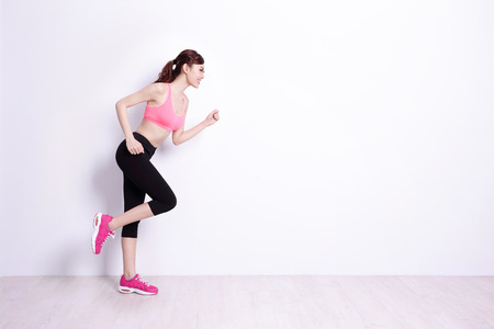 sport woman ready to run with white wall background,asian beauty