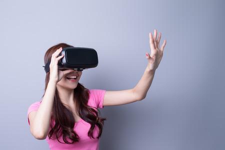 Glimlach gelukkige vrouw krijgt ervaring met VR-headset glazen virtual reality thuis veel gesticulerende handen, Aziatische schoonheid Stockfoto