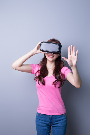 computer simulation: Smile happy woman getting experience using VR-headset glasses of virtual reality at home much gesticulating hands, asian beauty Stock Photo