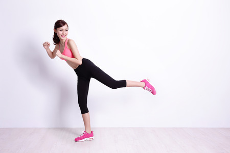 body shape: sport woman is doing exercise with white wall background,asian beauty