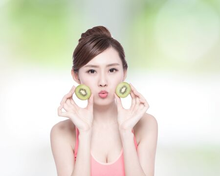 female beauty: Beauty woman and Kiwi fruit - The woman is dieting healthy with nature green background, asian female Stock Photo