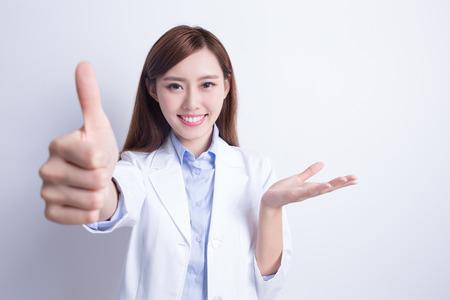 Donna sorridente dentista Colpo in su e mostrare qualcosa. con sfondo bianco. asiatico Archivio Fotografico - 54087404