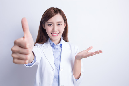 thump: Smiling dentist woman thump up and show something. with white background. asian
