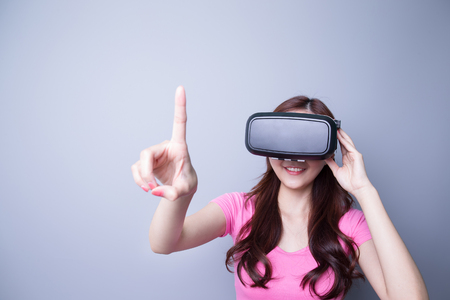 virtual reality simulator: woman using the virtual reality headset and one finger touch on air, Asian beauty