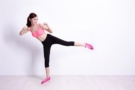 patada: sport woman is doing exercise with white wall background,asian beauty