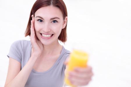 eten: Glimlach gelukkige vrouw greep sinaasappelsap met een witte achtergrond, gezonde leefstijl concept