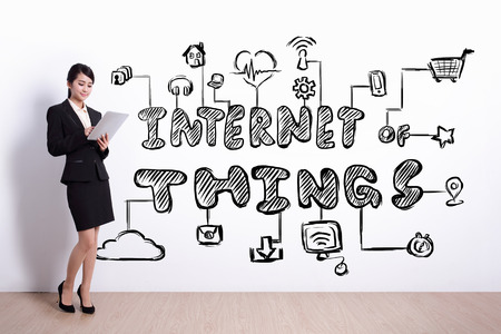woman tablet pc: business woman hold computer with drawing internet of things icon and text on white wall background, asian Stock Photo