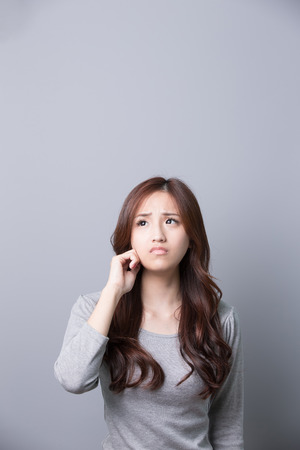 upset: unhappy woman think something isolated on gray background, asian beauty