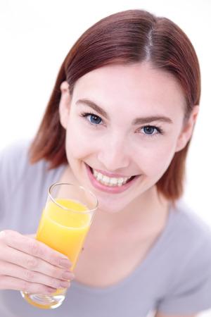 niña comiendo: Sonreír zumo de naranja asimiento de la mujer feliz con fondo blanco, el concepto de estilo de vida saludable