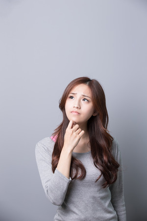 ongelukkige vrouw denkt dat er iets geïsoleerd op een grijze achtergrond, Aziatische schoonheid