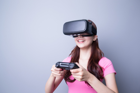 Happy woman playing games with the virtual reality headset, Asian beauty Stock Photo