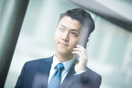 businessman in office: Business man talking on smart phone in front of the office window,asian