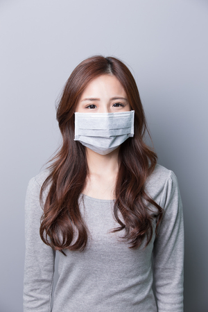 A Woman wears a mask , illness, asian beauty,gray background
