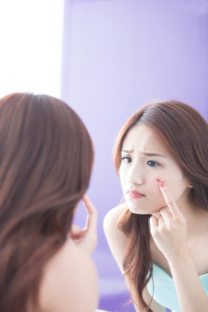 skin care woman: Face Skin Problem - skin care woman unhappy touch her acne and look mirror. asian beauty Stock Photo