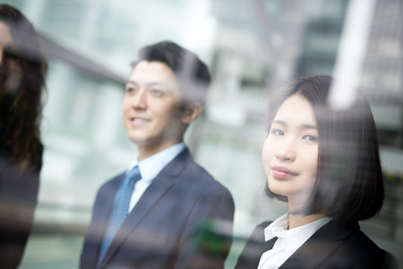 businessman in office: Business people team meeting in front of the office window, asian and caucasian