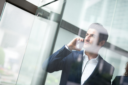 phone business: Business man talking on smart phone in front of the office window