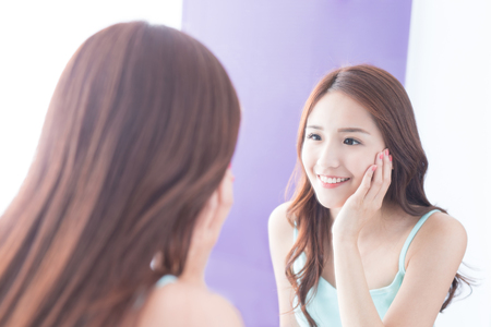 mirror: Beautiful skin care woman smile and look mirror. asian beauty