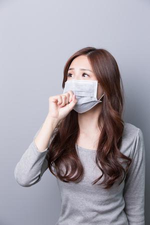 Kobieta nosi maskę i szukać czegoś, choroba, azjatyckie piękności, szare tło