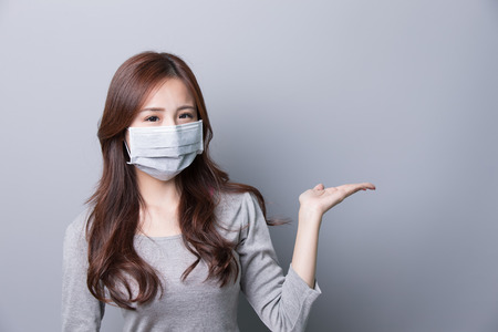 sneeze: A Woman wears a mask and show something, illness, asian beauty,gray background