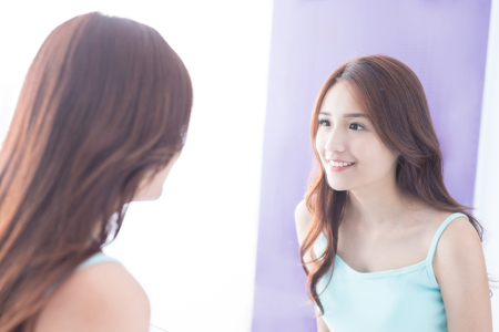 skin beauty: Beautiful skin care woman smile and look mirror. asian beauty
