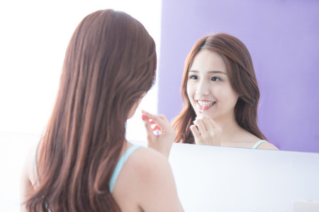 dental mirror: Close up of Smile woman clear teeth by floss and look mirror. great for health dental care concept. asian beauty