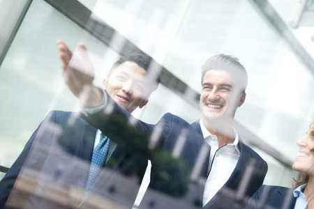 talk show: business people group meeting pointing something in front of the office window, asian people,european